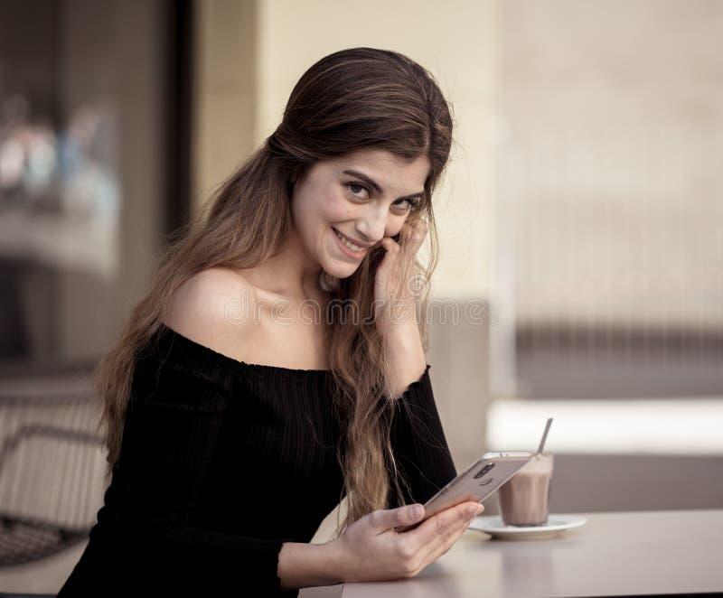 Привлекательная молодая женщина беседуя и датируя на умном мобильном телефоне в кофейне вне улицы города стоковое фото