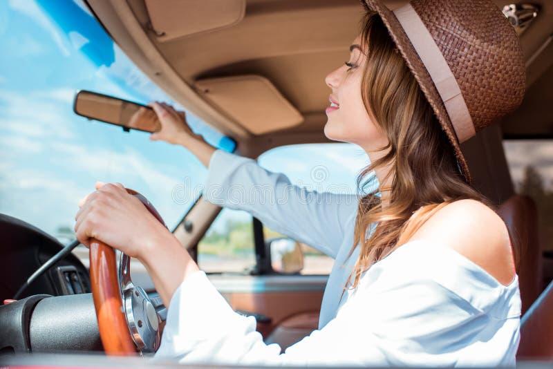 привлекательная молодая женщина в шляпе управляя автомобилем во время стоковая фотография rf