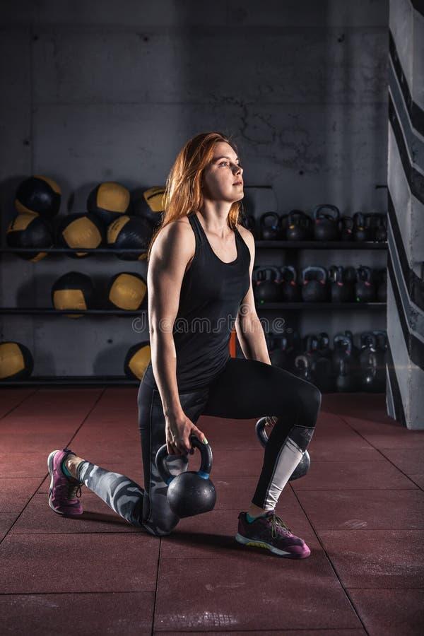 Привлекательная молодая женщина делая тренировки с kettlebell стоковое фото