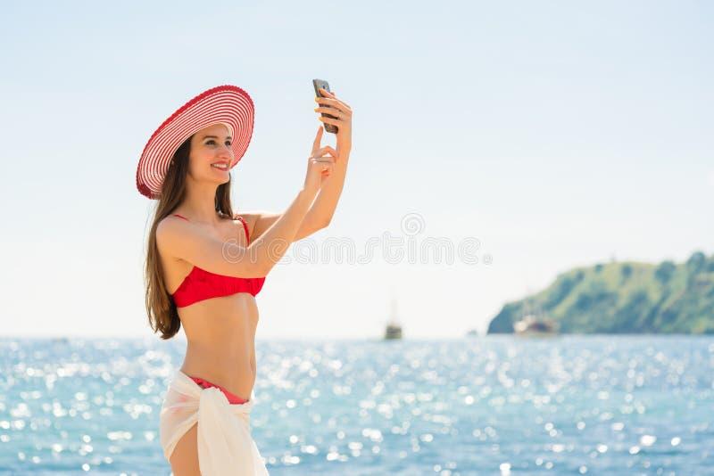 Привлекательная молодая женщина делая selfie на пляже во время vacat стоковое изображение