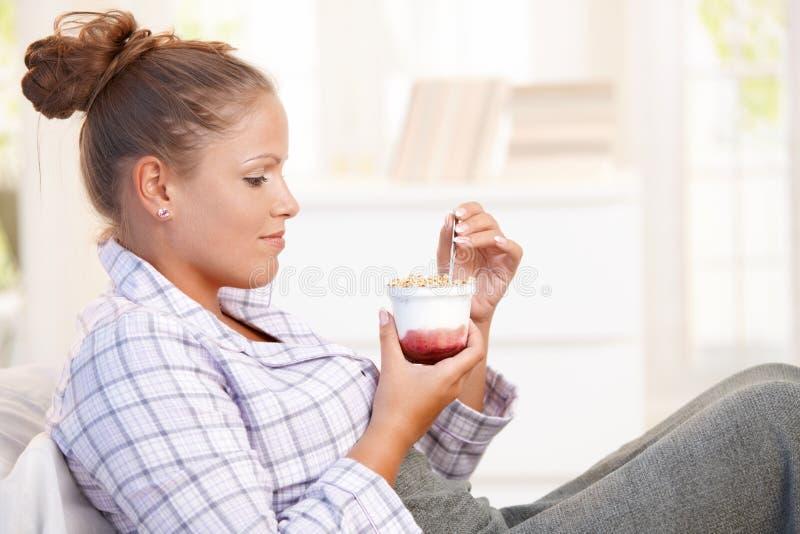 Привлекательная молодая женщина есть югурт в кровати стоковое изображение