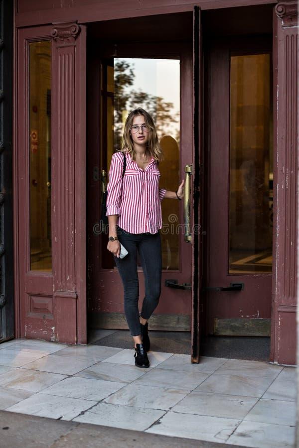 Привлекательная молодая женщина идет через вращающаяся дверь стоковое фото rf