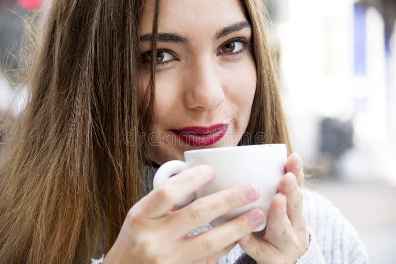 Привлекательная молодая женщина имеет кофе на улице с предпосылкой жизни улицы во времени осени стоковое фото rf