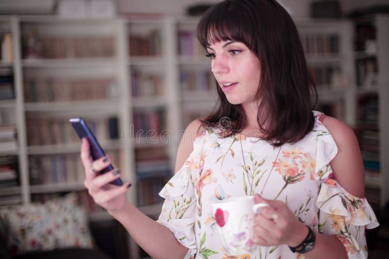 Привлекательная молодая женщина используя совершенно новый смартфон стоковое изображение rf