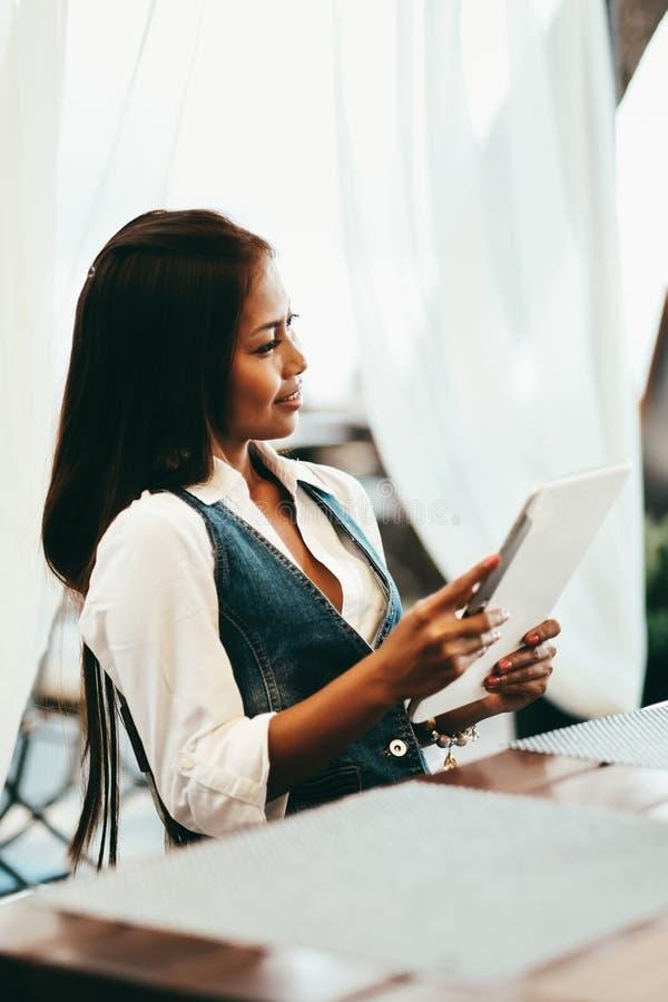 Привлекательная молодая женщина используя цифровую таблетку пока выпивающ кофе в кафе стоковая фотография