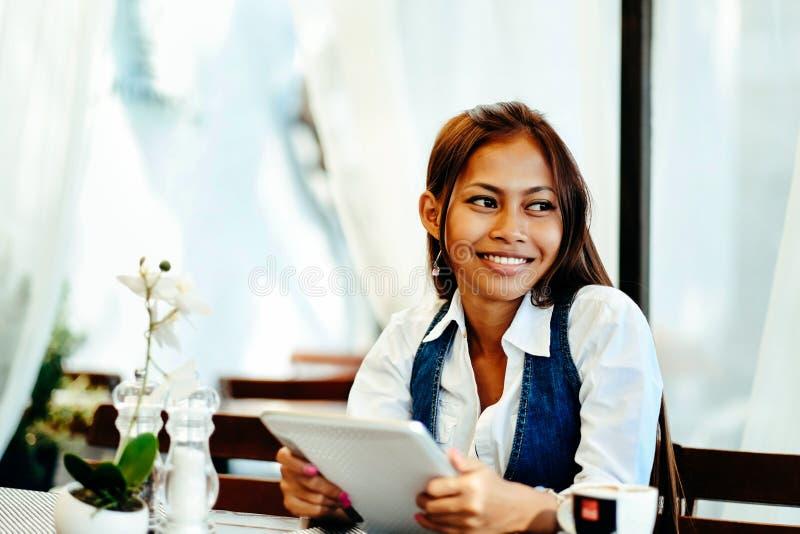 Привлекательная молодая женщина используя цифровую таблетку пока выпивающ кофе в кафе стоковое изображение