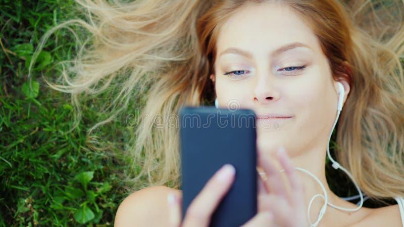 Привлекательная молодая женщина лежит на траве, наслаждается smartphone Волосы красиво лежат на лужайке стоковая фотография