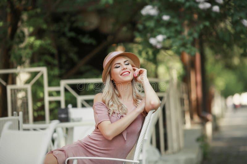 Привлекательная молодая женщина наслаждаясь ее снаружи времени в парке с заходом солнца в предпосылке стоковое фото