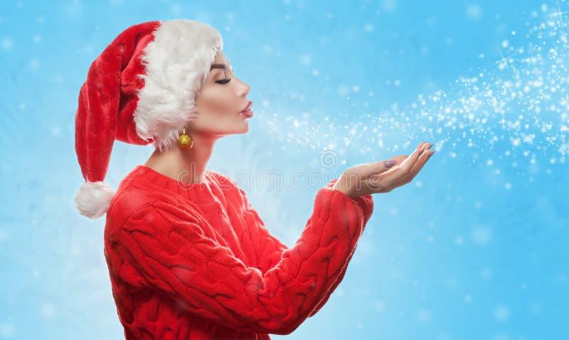 Привлекательная молодая женщина носит красную шляпу Санта Клауса на ее голове и в красном празднике свитер дует снежинки и сверкн стоковые фото