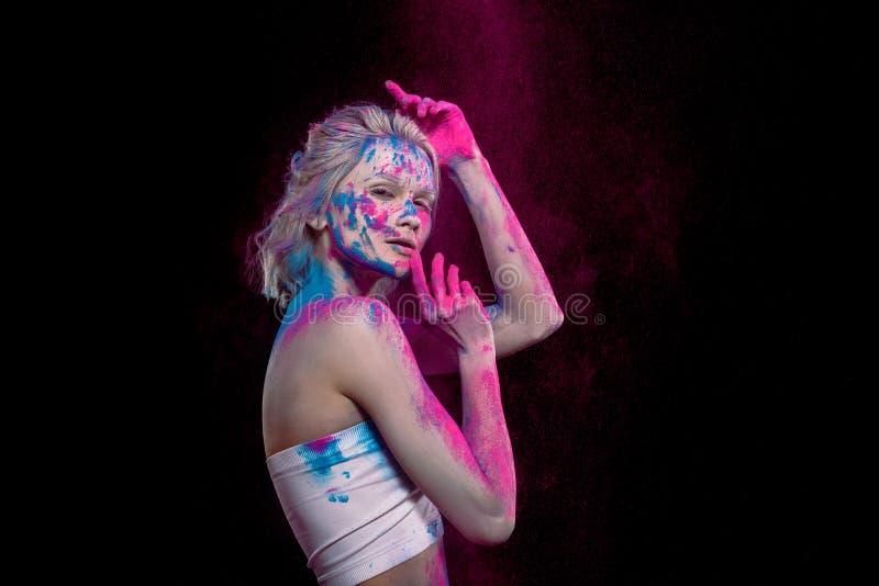 привлекательная молодая женщина представляя в пинке и голубой краске holi стоковое фото