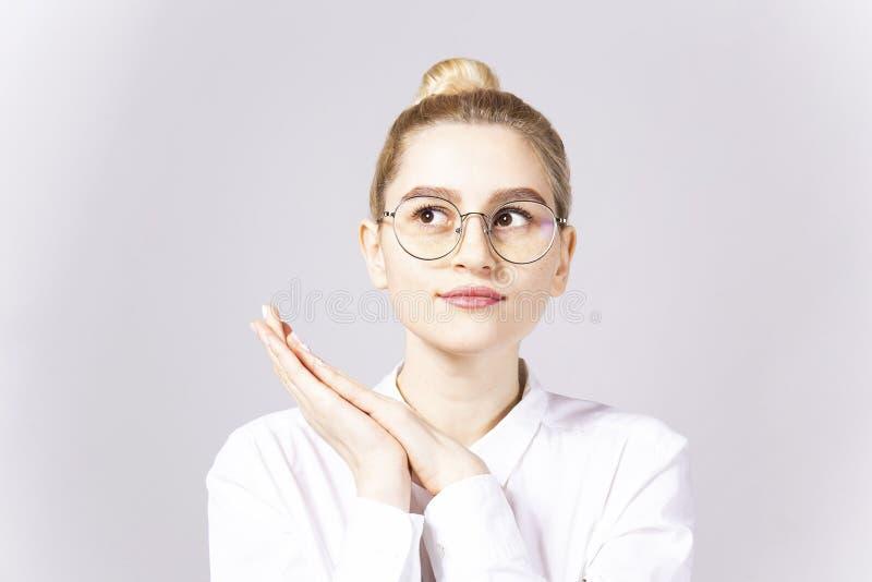 Привлекательная молодая женщина представляя над серой предпосылкой стоковые изображения