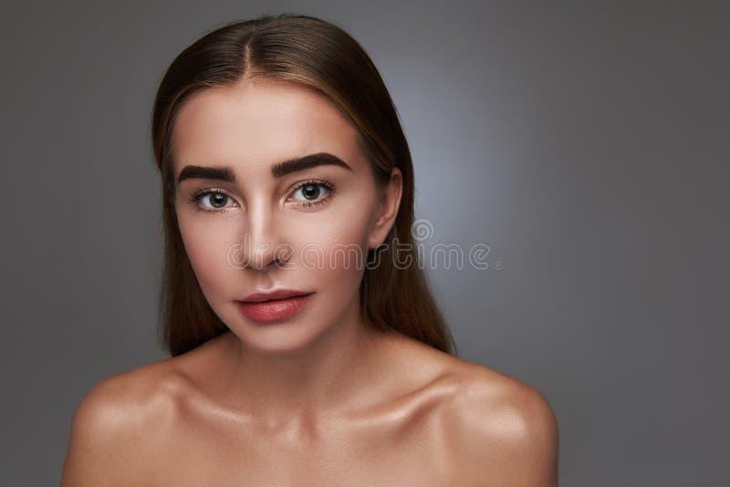 Привлекательная молодая женщина представляя против серой предпосылки стоковая фотография