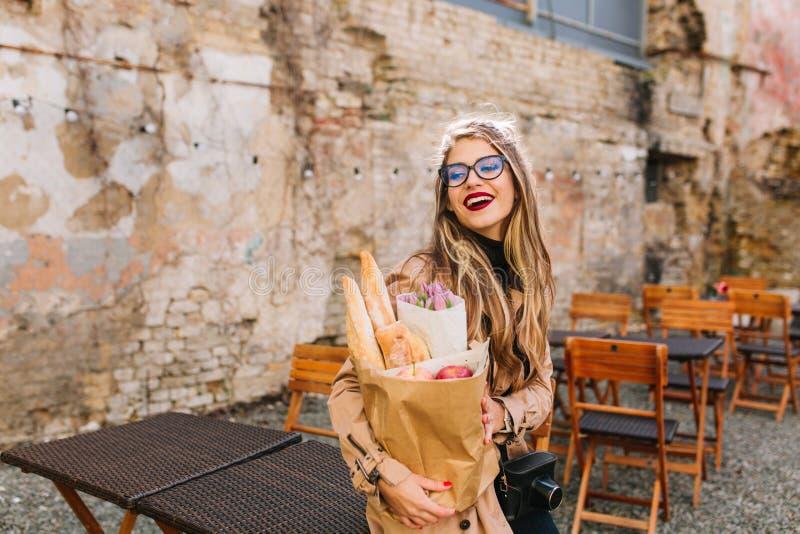 Привлекательная молодая женщина пришла к на открытом воздухе кафу после похода в магазин за едой и взглядов прочь Стильная белоку стоковая фотография