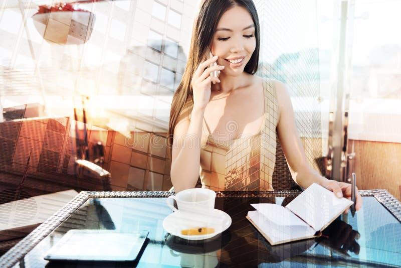 Привлекательная молодая женщина смотря ее извещения стоковая фотография rf