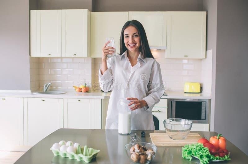 Привлекательная молодая женщина стоит в кухне и представлять Она смотрит камеру и усмехаться Девушка держит чашку молока в одной  стоковая фотография rf