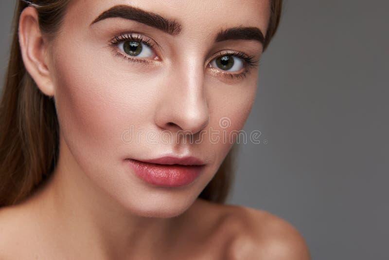 Привлекательная молодая женщина с естественным макияжем изолированная на серой предпосылке стоковые фотографии rf