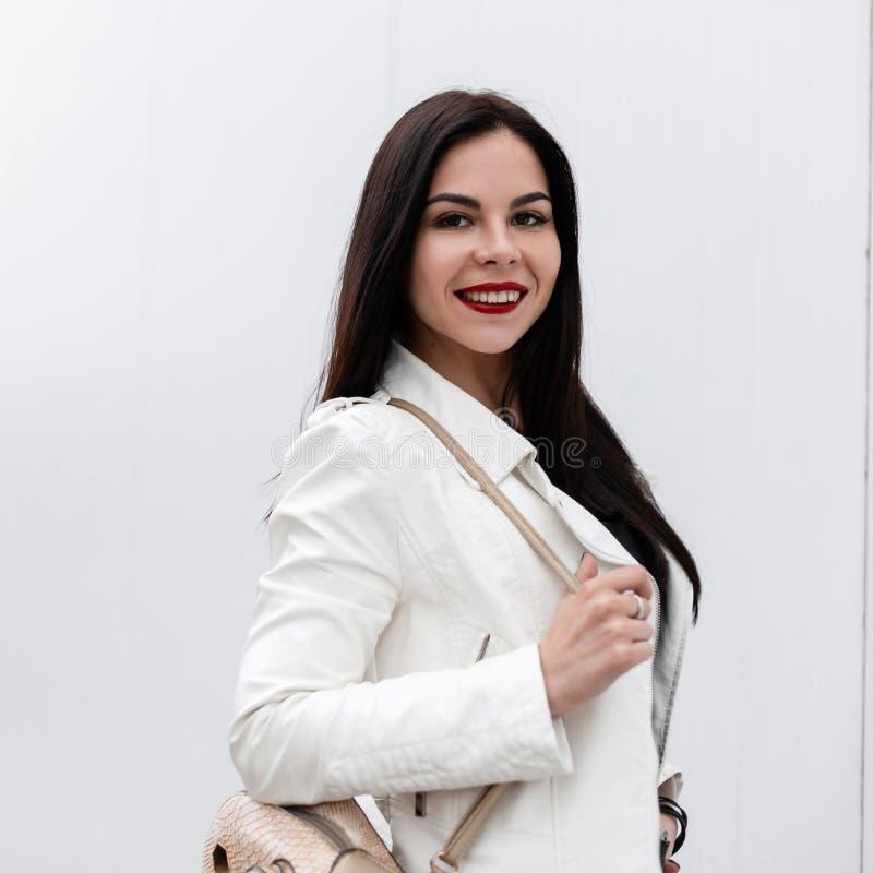 Привлекательная молодая женщина с красивой улыбкой в модной белой кожаной куртке с рюкзаком золота стоит стоковое фото
