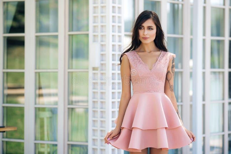 Привлекательная молодая женщина с красивой улыбкой в розовом платье позирует в уличном кафе стоковые изображения