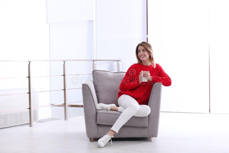 Привлекательная молодая женщина с чашкой чаю в кресле стоковые изображения