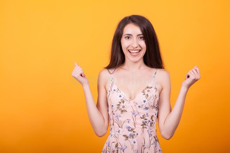 Привлекательная молодая женщина smilling на камере в студии над желтым платьем предпосылки вкратце стоковые фото