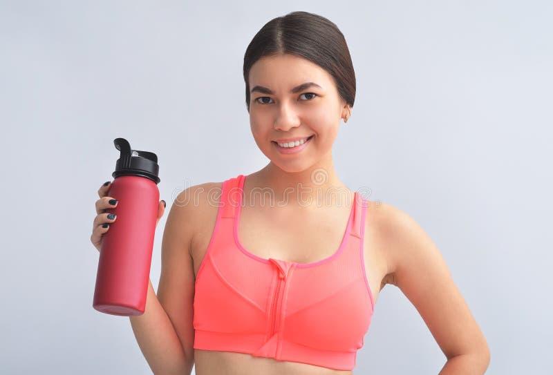 Привлекательная молодая спортсменка, стоящая над серым фоном стоковые фото