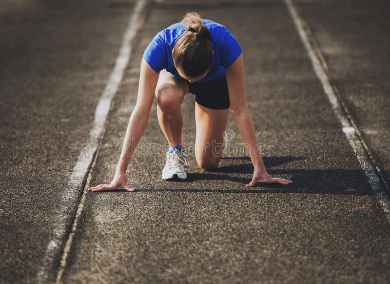 Привлекательная молодая Sporty девушка готовая для того чтобы побежать спринт стоковое фото