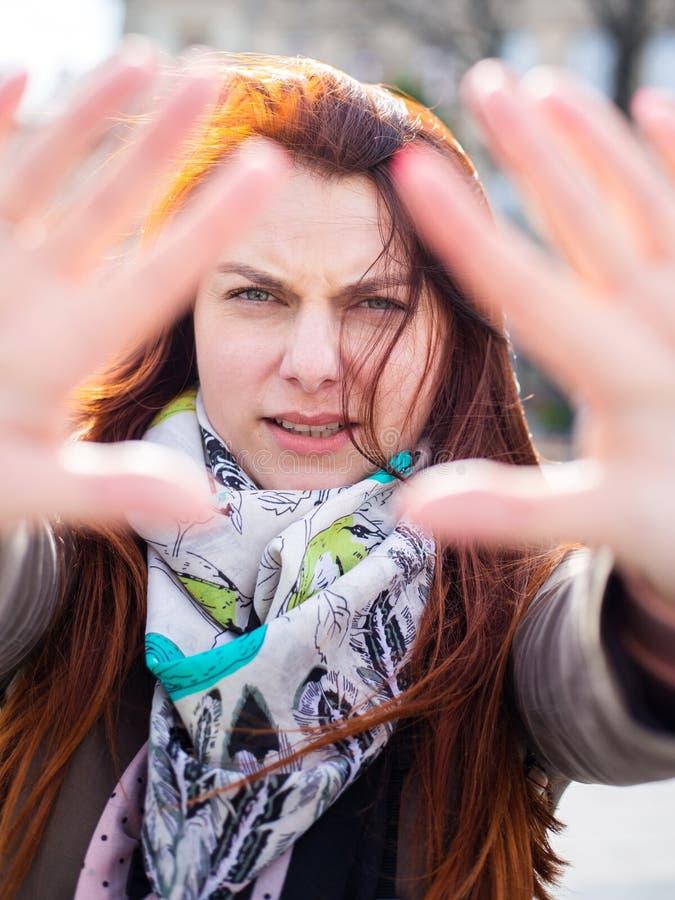 Привлекательная определенная женщина redhead серьезная и, кладущ руку во фронт, останавливает жест, отказывает концепцию стоковое изображение rf