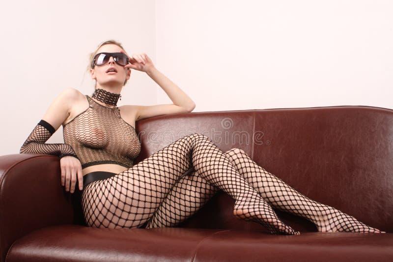 привлекательная сексуальная сидя женщина солнечных очков софы Стоковое фото RF