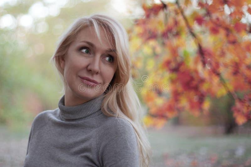 Привлекательная середина постарела кавказская женщина с зелеными глазами на парке осени, усмехаясь, самостоятельно вскользь износ стоковые изображения rf