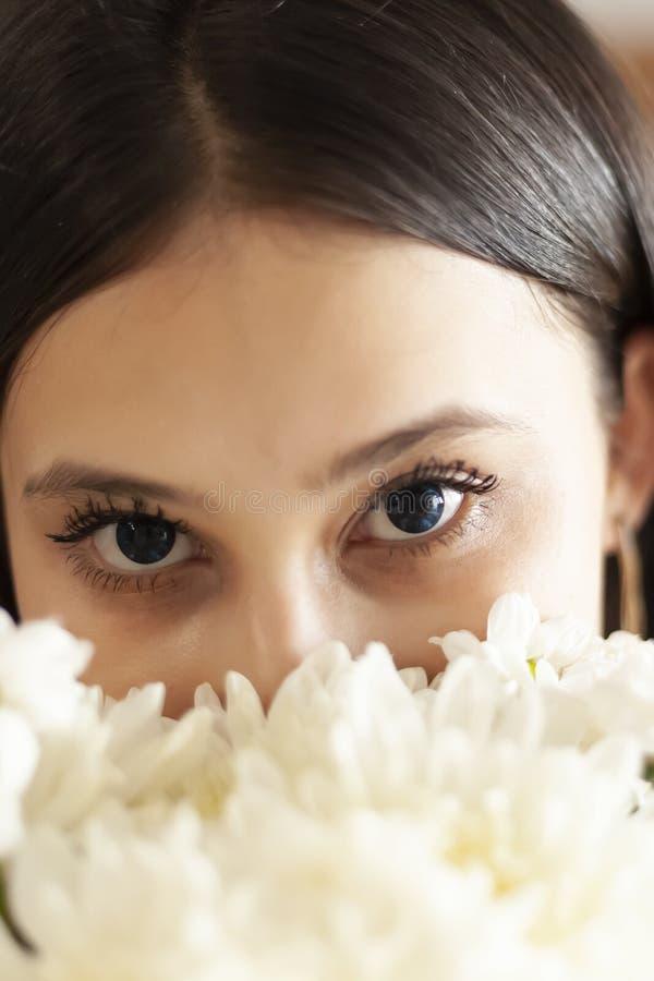 Привлекательная средне-восточная девушка с красивыми глазами смотрит в камеру из-за букета цветов стоковое изображение rf