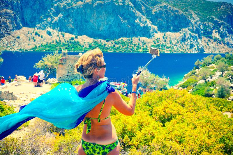 Привлекательная средняя достигшая возраста женщина делая фото selfie с ручкой selfie в горячем летнем дне на острове Kamelya стоковая фотография rf