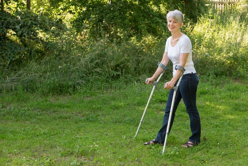 Привлекательная старшая женщина идя с костылями стоковое фото