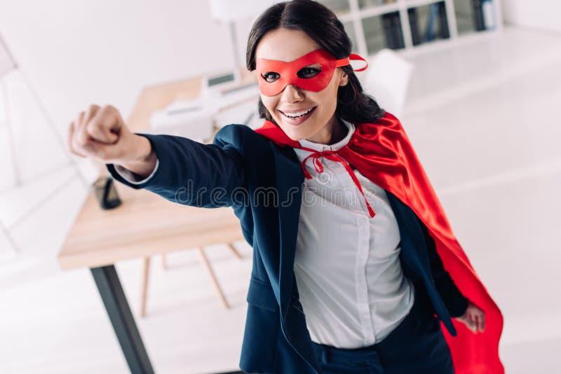 привлекательная супер коммерсантка в накидке и маска стоя с рукой вверх стоковые изображения