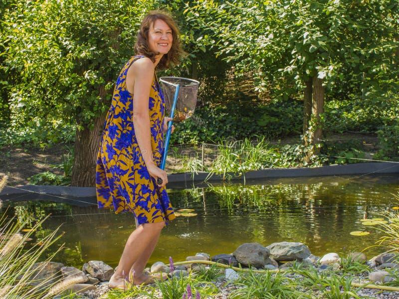 Привлекательная счастливая активная женщина с листьями ветроуловител-сети улавливая i стоковые изображения