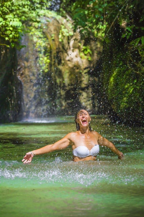 Привлекательная счастливая белая туристская женщина наслаждаясь играть с водой и выплеск на тропических экзотических праздниках л стоковая фотография