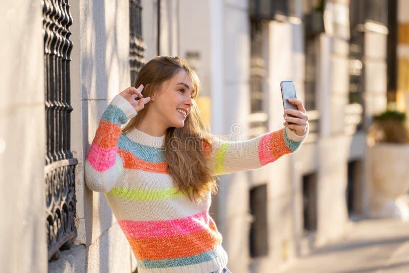 Привлекательная счастливая молодая женщина подростка фотографируя selfie по умному телефону в городе стоковые фото