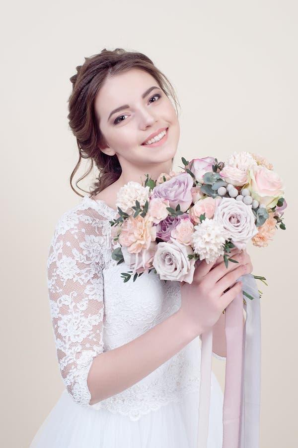 Привлекательная усмехаясь женщина держа букет цветков нося в роскошном платье свадьбы изолированном на предпосылке стоковые изображения rf