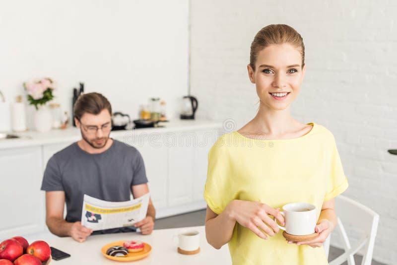 привлекательная усмехаясь женщина держа кофейную чашку и ее парня стоковые фото
