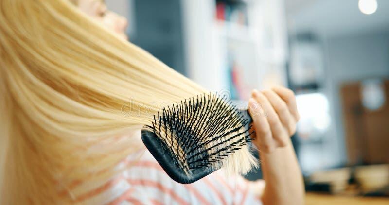 Привлекательная усмехаясь женщина чистя ее волосы щеткой стоковая фотография rf