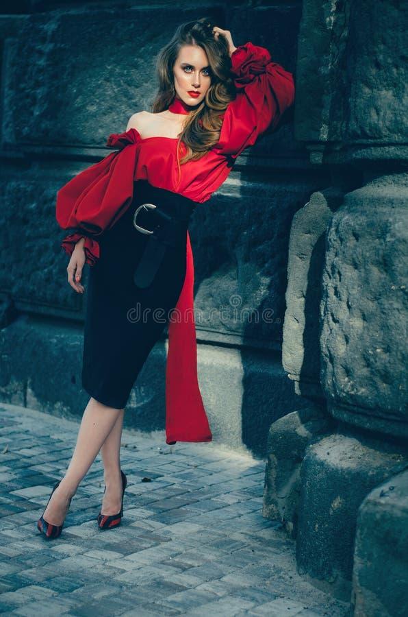 Привлекательная худенькая женщина в холеной элегантной блузке и черной юбке идя через город фото серии стоковое фото