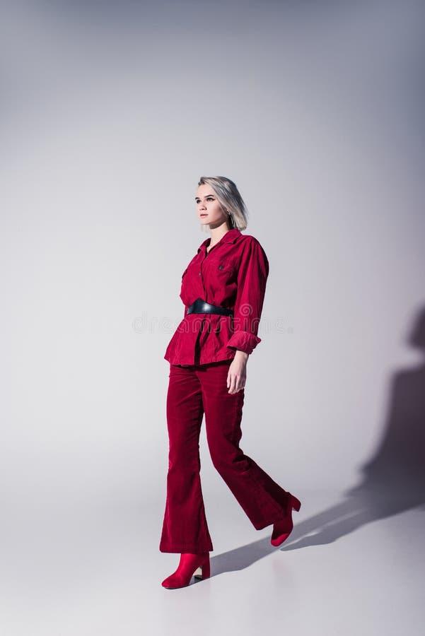 привлекательная элегантная девушка в красных ультрамодных одеждах представляя для всхода моды стоковое изображение rf