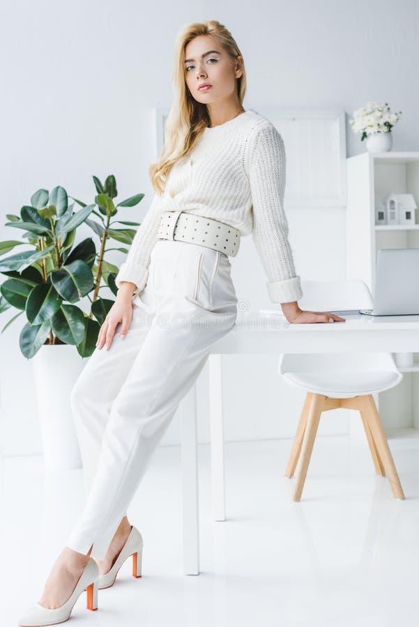 привлекательная элегантная коммерсантка представляя в белых одеждах стоковые изображения