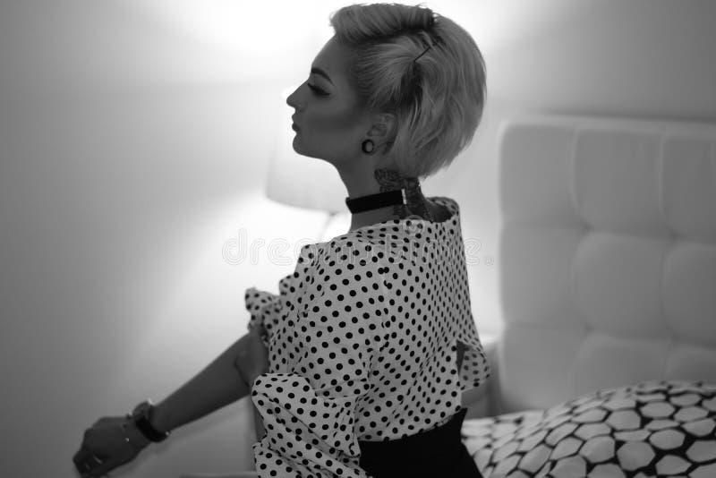 Привлекательная alluring молодая белокурая женщина лежа на кровати в спальне, photoshoot серой шкалы стоковое фото