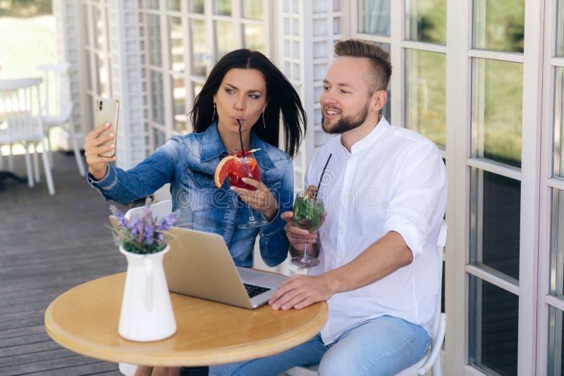Привлекательное брюнет встречанное с другом в кафе, пить очень вкусный коктеиль и уничтоженном Selfie на ее smartphone стоковое фото