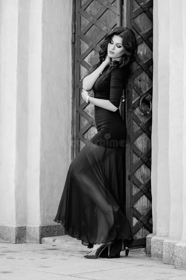 Привлекательное брюнет в черном платье стоит полностью рост на предпосылке здания способ простыни кладет детенышей белой женщины  стоковые фото