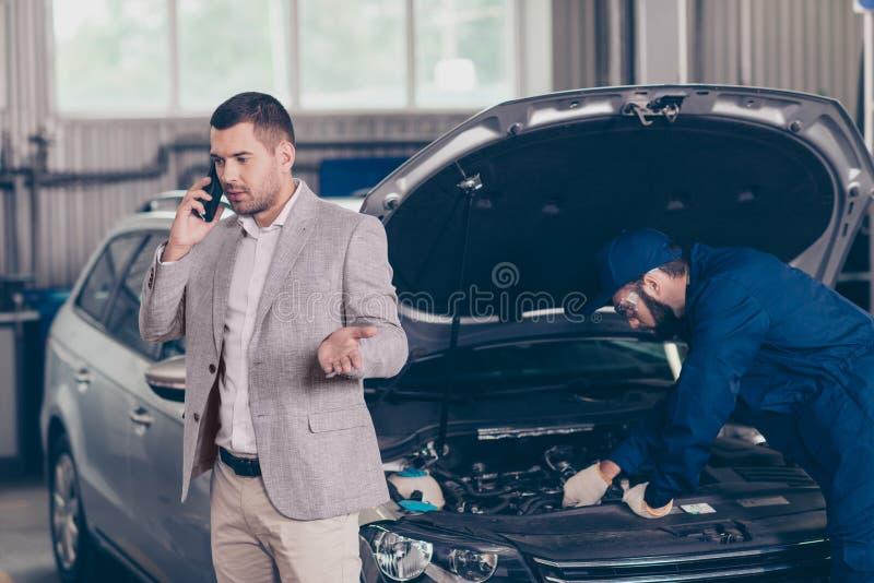 Привлекательное серьезное занятое предприниматель автомобиля, которого получает оценивать  стоковая фотография