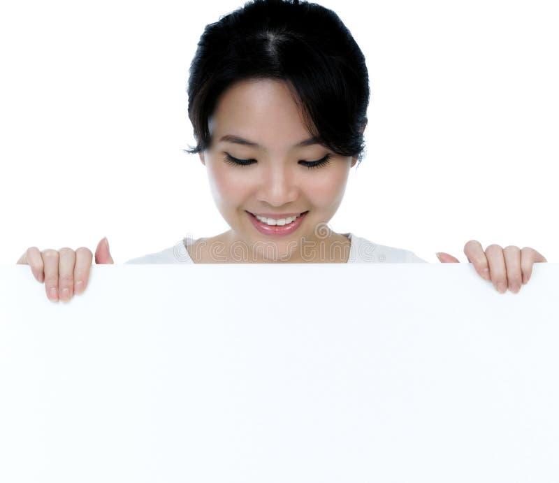 привлекательное удерживание афиши смотря женщину стоковые фото
