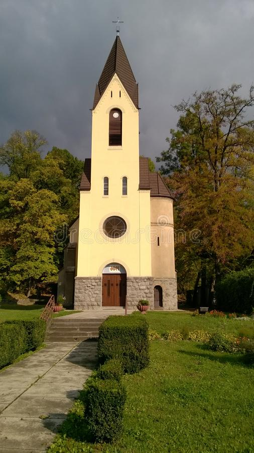 Привлекательно старомодная маленькая церковь страны сидя в зеленом луге окруженном деревьями летом стоковое изображение rf