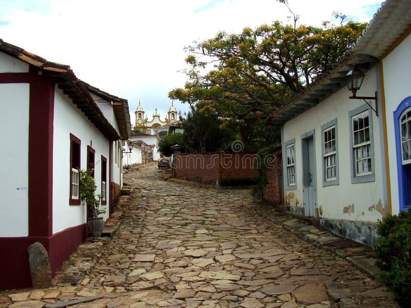 Привлекательно старомодный колониальные дома и магазины в тихой улице водя к церков стоковая фотография