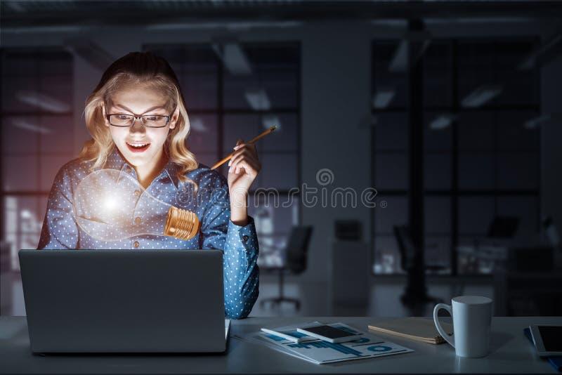 Привлекательные белокурые нося стекла в темном офисе используя компьтер-книжку M стоковое изображение rf